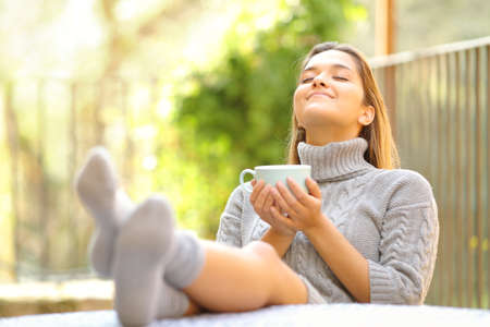 Carefree woman breathing fresh air relaxing drinking coffee in a garden at home in winter Archivio Fotografico