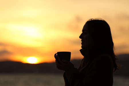 Profile silhouette of a woman holding coffee mug at sunset on the beach