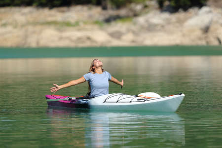 Happy woman celebrating kayak day outstretching arms in a lake