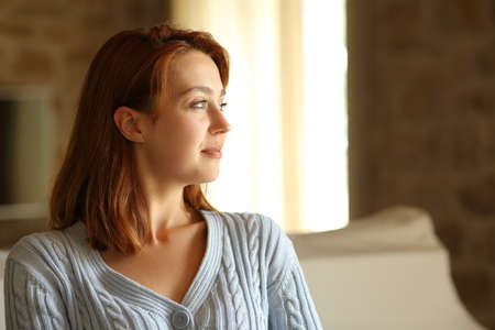 Confident tenant looking at side through a window at home