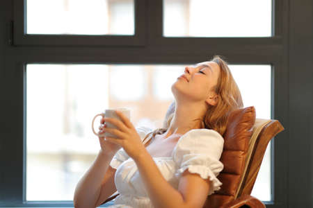 Happy woman relaxing sitting on a seat breathing fresh air holding coffee cup in the living room at home