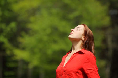 Relaxed woman in red breathing fresh air standing in a forest