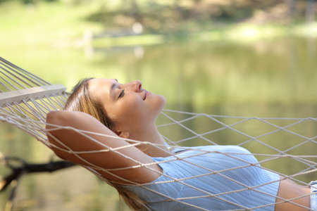 Profile of a woman resting lying on hammock relaxing beside a lake in the mountain