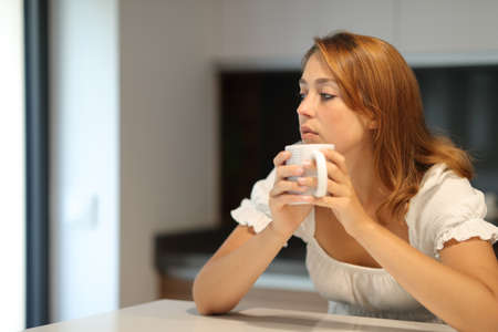 Pensive serious woman holding coffee mug looking away at home Archivio Fotografico