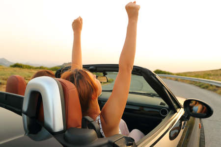 Two women in a convertible car driving and raising arms in a mountain road