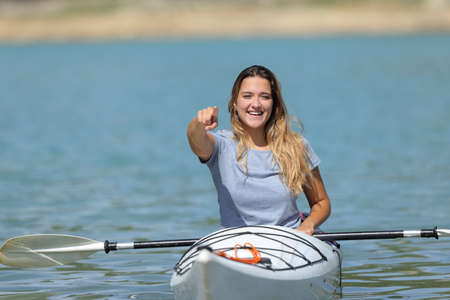 Front view of a happy woman in a kayak pointing at camera in a lake