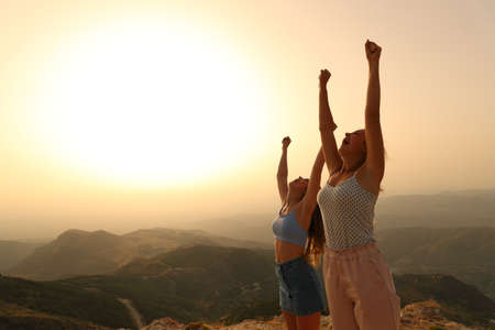 Two happy friends raising arms celebrating vacation at sunset in the mountain