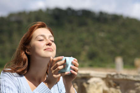 Woman enjoying outdoors holding a coffee cup in the mountain Archivio Fotografico