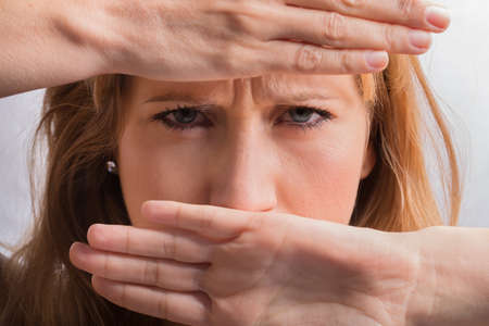 agressive: angry female face covered with hands Stock Photo
