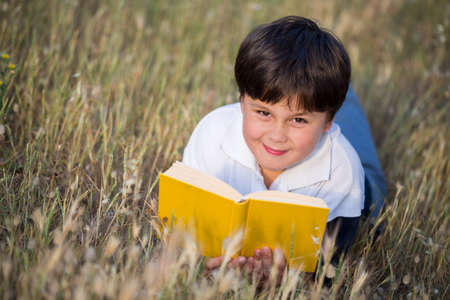 dutiful: little boy reading book in the park, selective focus