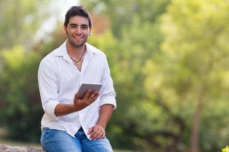 adult  male: young man using internet outdoor in the park,selective focus