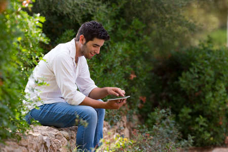 man searching: young latin man searching internet coverage outdoor,selective focus Stock Photo