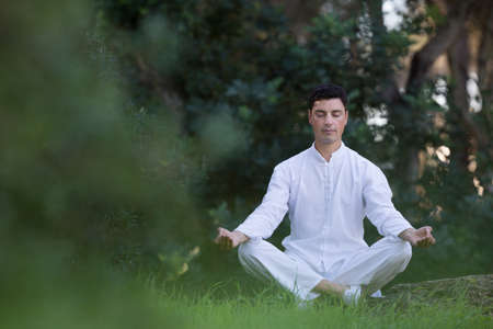 soul searching: Serene young man sitting in the park doing meditation Stock Photo