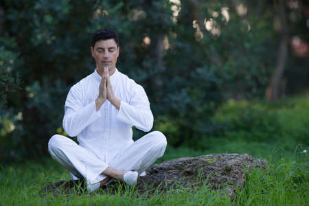 soul searching: young man doing meditation in the park, selective focus on the hands Stock Photo