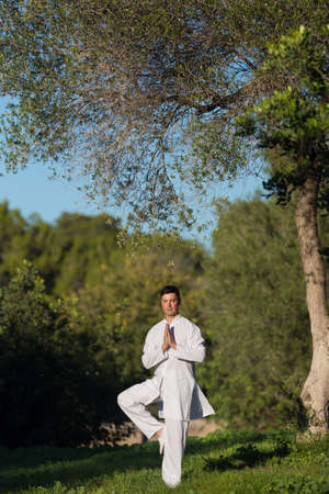 soul searching: young man doing yoga in the park, selective focus
