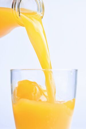 a bottle of orange juice pouring on glass photo