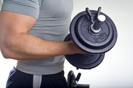 Healthy man hard workout of biceps in gym photo