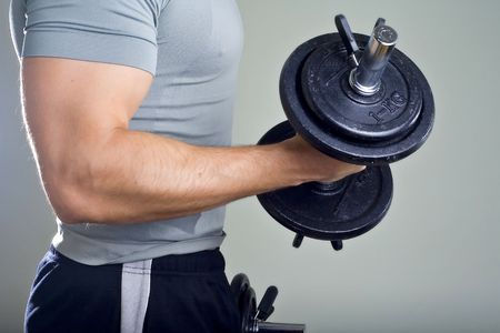 Healthy man hard workout of biceps in gym