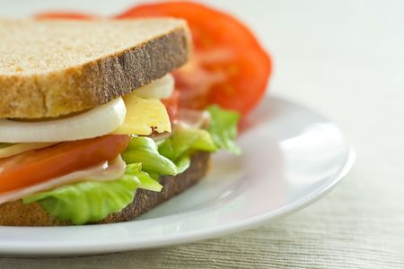 A delicious and healthy sandwich turkey ham cheese lettuce tomato and onion photo