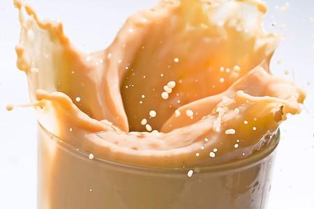 ice cream glass: Ice Cube falling on glass of milk cream splashing