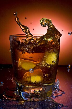 glass of alcoholic beverage whith ice cubes photo