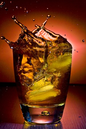 glass of alcoholic beverage whith ice cubes