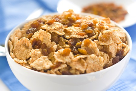 bowl of cereal with raisins, milk and orange juice Stock Photo