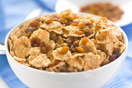 comiendo cereal: plato de cereal con pasas, leche y zumo de naranja Foto de archivo