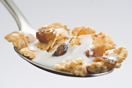 bowl of cereal with raisins and milk isolated photo