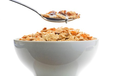corn flakes: bowl of cereal with raisins and milk isolated
