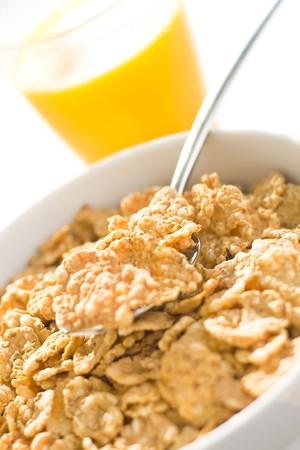 bowl of cereal with raisins, milk and orange juice photo