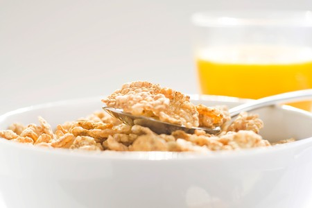 bowl of cereal with raisins, milk and orange juice photo