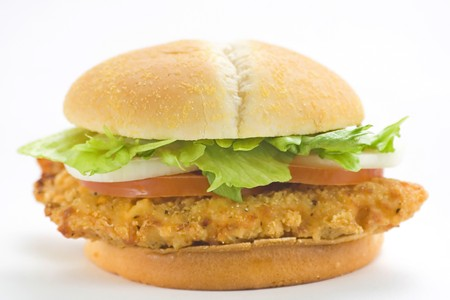 chicken sandwich: crisp chicken burger with tomato onion cheese lettuce isolated Stock Photo