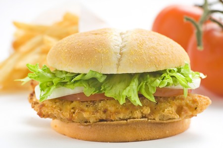 fried snack: crisp chicken burger with tomato onion cheese lettuce isolated Stock Photo