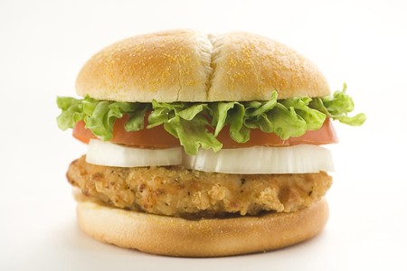 crisp chicken burger with tomato onion cheese lettuce isolated photo
