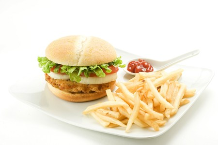 cheeseburger with fries: crisp chicken burger with tomato onion cheese lettuce isolated Stock Photo