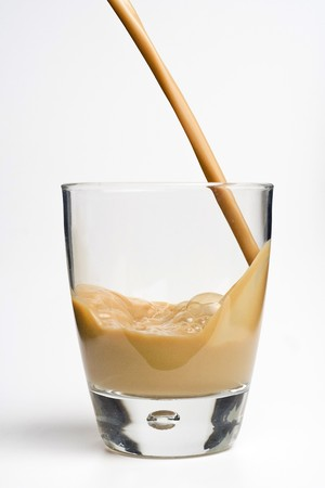 glass whiskey cream with ice cubes isolated over white photo