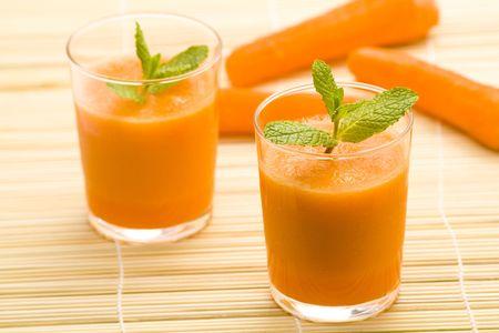 jus orange glazen: lekker en vers sap wortel en munt Stockfoto