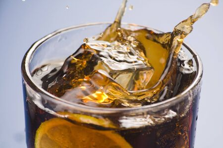 refreshing glass of cola with lemon and ice isolated photo