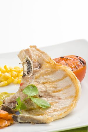 tasty pork chop with corn carrot tomato isolated photo