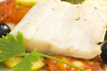 Filet de cabillaud cuit au four les tomates courgettes olives noires isolées