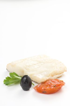 fillet of cod baked tomatoes zucchini black olives isolated photo