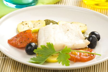 ling: fillet of cod baked tomatoes zucchini black olives isolated