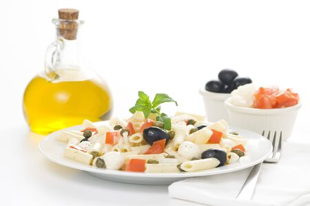 capers: fresh macaroni mozzarella olives capers tomatoes salad isolated Stock Photo