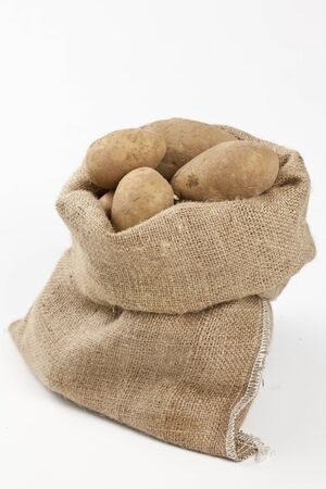 potatoe: Raw potatoes in burlap bag isolated over white background