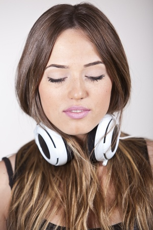 one eye closed: A Beautiful and cheerful young woman enjoying music
