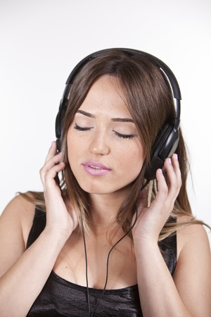 A Beautiful and cheerful young woman enjoying music Stock Photo - 13258911