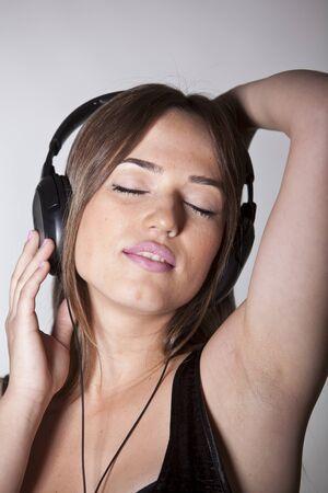 closed eye: A Beautiful and cheerful young woman enjoying music