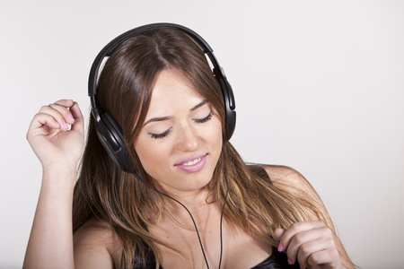 A Beautiful and cheerful young woman enjoying music Stock Photo - 13302658