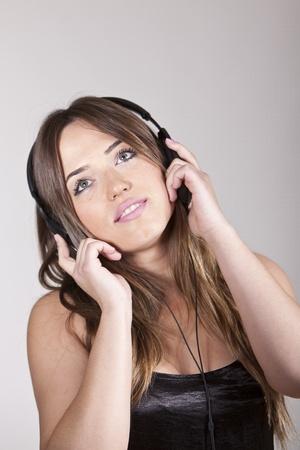 A Beautiful and cheerful young woman enjoying music Stock Photo - 13341580